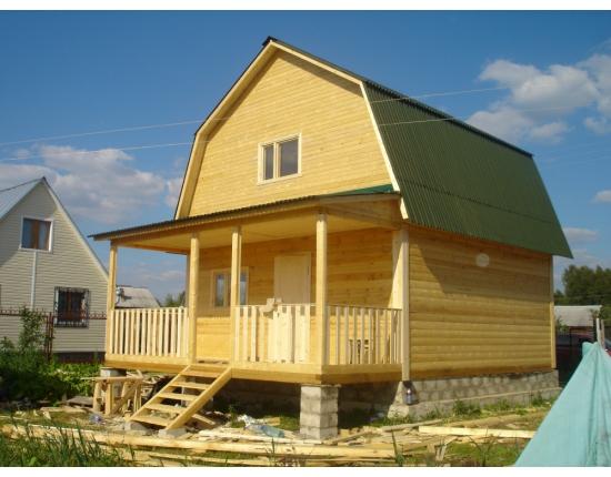 деревянный загородный дом с ломаной конструкцией крыши